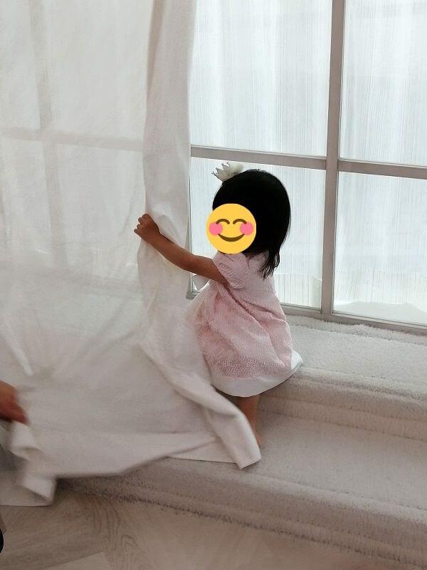 カーテンを使ってスタッフさんと「いないいないばぁ」をしている写真